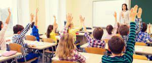 School children in class raising their hands